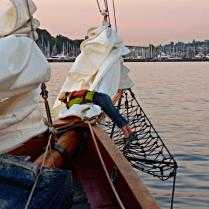 One of the crew on the Schooner Adventuress tying the sail to the bow sprit.