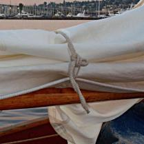 Sail tie made from three strand line on the Schooner Adventuress. The line is doubled and the strands separated out and them braided back together with a six strand flat braid.