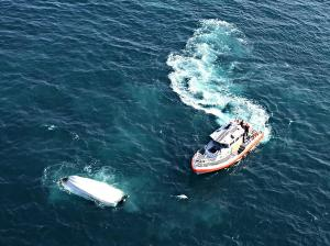 Crewmembers aboard a 45-foot Response Boat-Medium, from Coast Guard Station Charleston, S.C., approach an overturned boat, July 13, 2015, approximately 12 miles off the Charleston coast. The boat was found during a search for four overdue boaters who were later rescued by Station Charleston crews. (U.S. Coast Guard photo)