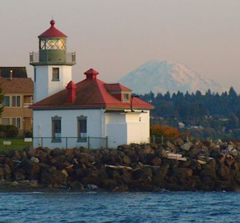 08-Alki Point Tradition has it that Hans Martin Hanson first set a lantern on the beach to provide a light to help vessels in 1868. In 1887 a Post Lantern was hung from a scaffold and became the first official light. Post Lanterns could burn continuously for eight days and in some remote locations they were refueled and serviced weekly. The original Alki Point Post Lantern is on display at the Coast Guard Museum on the Coast Guard Base in Seattle. The lighthouse was built in 1913 and first lighted on June 1 of that year. The light was automated in 1984. Senior Coast Guard personnel live in the the lighthouse keepers homes.