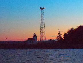 09-Point Robinson The first Aid To Navigation at Point Robinson was a fog signal dedicated on July 1, 1885. In 1887 a Post Lantern with a red lens was installed on a 25 foot tall post near the fog signal. A wooden tower was built in 1894 to raise the light to 31 feet to aid vessel traffic from the south. The current lighthouse was built in 1915 that raised the light to 38 feet. The lighthouse and fog signal was automated in 1989 and modern optics were added in 2007. The original Fresnel lens remains in the lantern room.